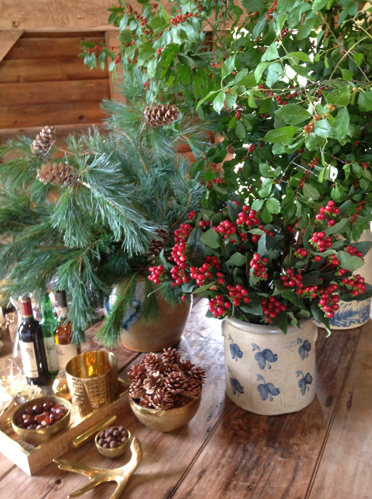 The Drinks table featured stoneware filled with pine and red hypericum berries.  The rustic wood table was the perfect place to highlight Aerin's gold containers filled with nuts and pinecones